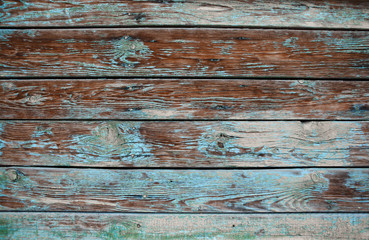 Old shabby wooden background with cracks and layers of paint