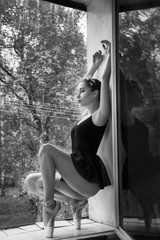 young ballerina in satin ballet shoes posing on a window. on a autumn landscape background. black and white