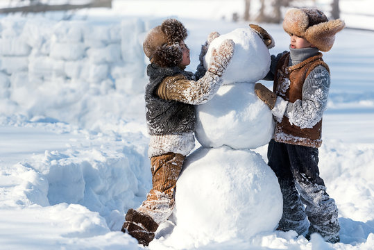 Children shape the snowman in the backyard of the house