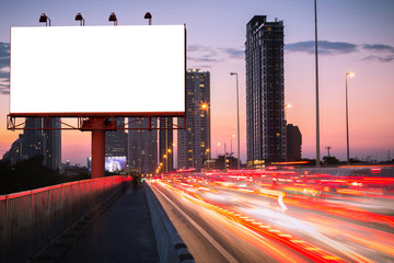 Blank billboard with light trails, street and urban in the twilight or night - can advertisement for display or montage product or business.