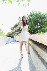 asian woman who wear ballet dress and toe shoe is standing with right foot toe