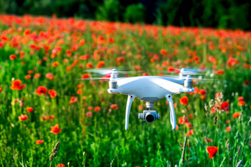 White quadrocopter, is flying high in the air, to take photos and record footage from above, in red poppy field. Drone with four motors, propellers, camera, warning lights. Romantic flowers background