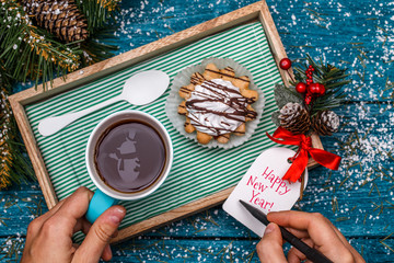 New Year's photo of tea with picture of snowman, cake