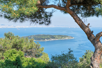 Aerial view of Sedef Island (Mother of Pearl Island) framed by green trees from Buyukada island. Both are neighbourhoods in the Adalar district of Istanbul, Turkey