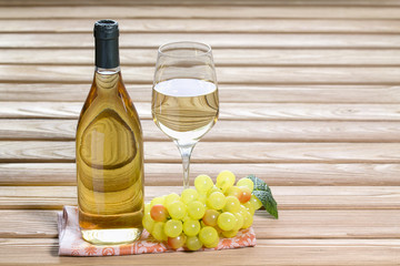 Bottle and glass of white wine are stand on table together bunch of grapes