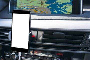 Smartphone in a car use for Navigate or GPS. Driving a car with Smartphone in holder. Mobile phone with isolatede white screen. Blank empty screen. Empty space for text. modern car interior details.