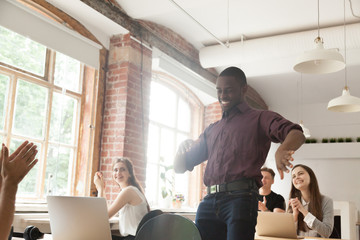 African american office worker dancing surrounded by coworkers. Happy entrepreneur performing victory dance, celebrating great achievement at work. Team of coworkers cheering him by clapping hands.