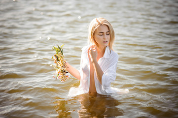 Nude portrait of pretty blond girl in white wet shirt