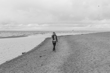 black and white, on the beach on a cloudy day walks an attractive girl