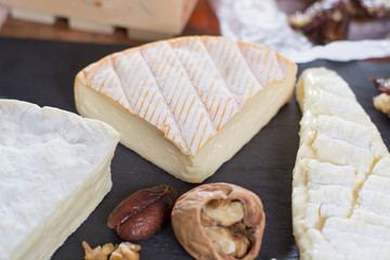 French soft cheeses - camembert, marcaire, munster, brie - delicious dessert with nuts and dried fruits