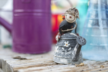 Quirky ornamental children's character riding on a rustic flower decorated watering can in a traditional English potting shed or green house