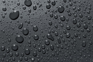 Closeup of raindrops on silvery surface, abstract background