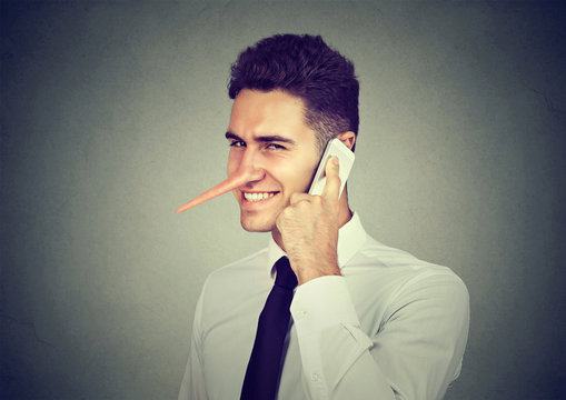 Sly young man with long nose talking on mobile phone isolated on gray wall background. Liar concept.