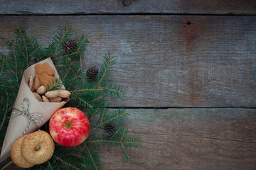 Red and yellow apple on a branch of a Christmas-tree with cookies, ginger-snaps, nuts, cones and dried cranberries. Old wooden background
