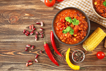 Bowl with delicious chili con carne on wooden background