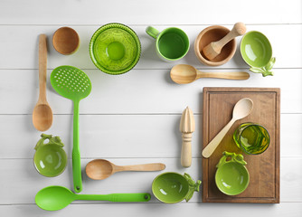 Kitchen utensils and tableware on wooden background