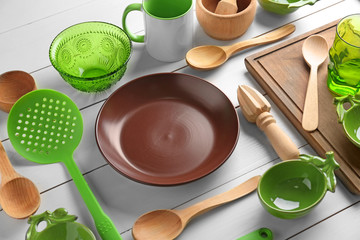 Kitchen utensils and tableware on wooden table
