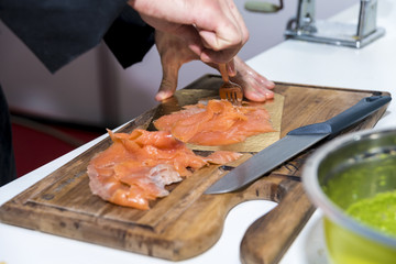 The chef prepares and serves salmon fillets