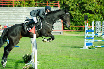 Young man jockey ride beautiful black horse and jump over the crotch in equestrian sport.