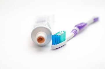 On a white background lies toothpaste and brush