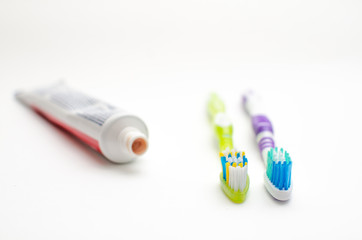 On a white background lies toothpaste and two brushes