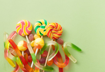 Colored candies for Halloween on a green background