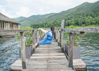 Happy woman in a short dress enjoys on bridge wood with lake and mountain view