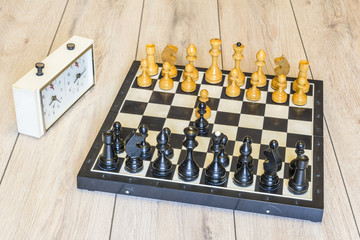 Old wooden chess pieces and chess clock on a wooden background.