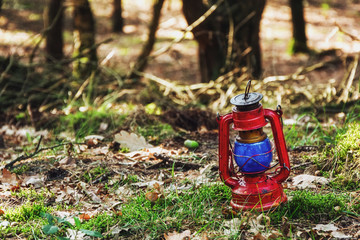 Red lantern with blue glass left in the woods