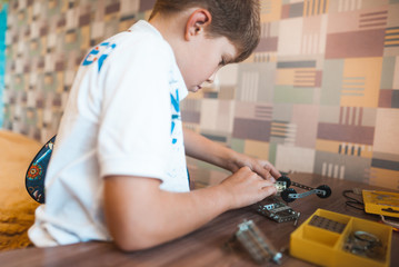 Little cute boy plays with mechanical constructor at the table
