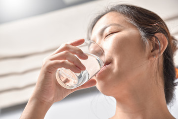 Woman holding glass of water.