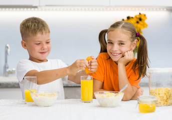 Brother squeezes orange juice for breakfast his sister