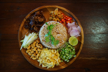 Obraz Kao Cluk Ka Pi or Mixed Cooked Rice with Shrimp Paste on the wooden round dish. Thai Traditional food. - fototapety do salonu