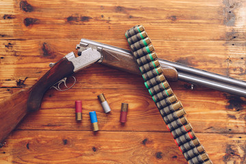 Hunting equipment. Shotgun and hunting cartridges  on wooden table.