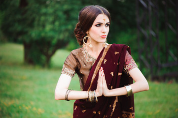 Indian girl with oriental jewellery and make-up henna applied to hand. Brunette Hindu model girl with Indian jewels.