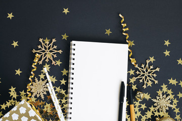 Christmas planning concept mock up. Notebook on black background with gold stars confetti, gift, serpentine and glitter snowflakes ornaments. Place for text flat lay