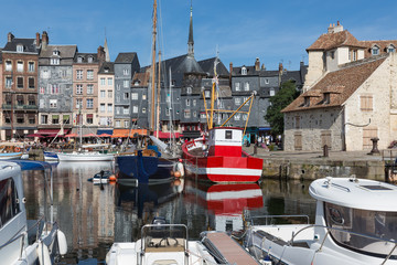 Saling boats and fishing ship in old medieval harbor of Honfleur, France