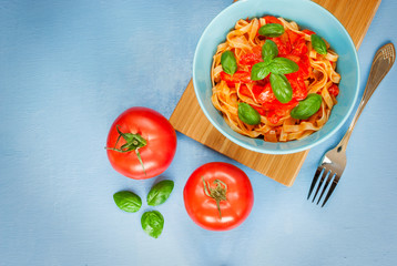 Tagliatelle with pepperonata sauce, basil leaves and tomatoes on side. Blue background, top view.