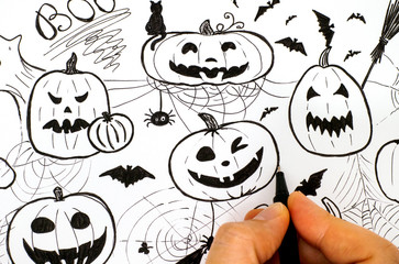 Woman hand with pen drawing Halloween concept.