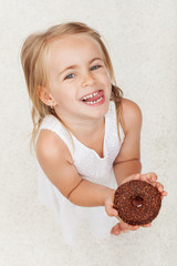 Happy little girl holding a chocolate covered doughnut - looking up with a broad smile