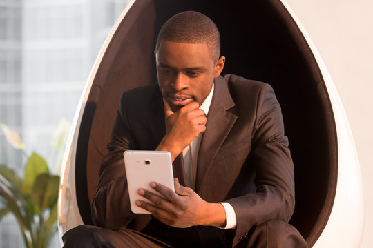 Portrait of successful pensive african american businessman in stylish suit sitting in futuristic egg chair using digital tablet. Handsome black model guy looking on phablet screen, reading e-book