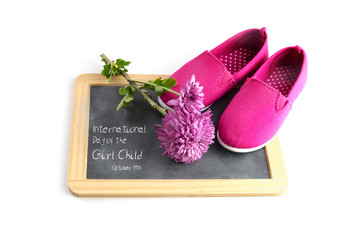 pink kid shoes and a flower on a writing blackboard isolated on a white background, text International Day of the Girl Child 11 October, copy space, selected focus