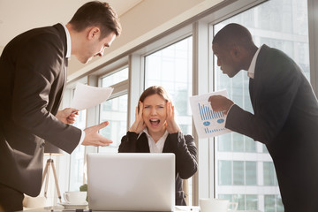 Businesswoman holding head with hands and screaming surrounded by worried colleagues with business documents in hands. Stressed female office worker getting reprimand from superiors, missing deadline