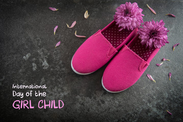 pink kid shoes and flowers on a dark slate background, text  International Day of the Girl Child,  concept date 11 October, copy space, selected focus