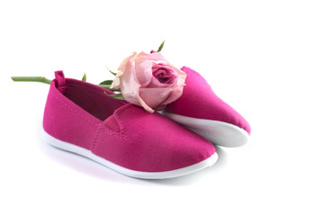 pink kid shoes and a rose isolated on a white background, concept International Day of the Girl Child on 11 October, copy space