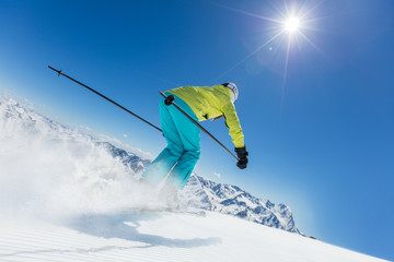 Fototapete - Young woman skier running down the slope in Alpine mountains