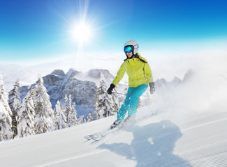 Young woman skier running down the slope in Alpine mountains