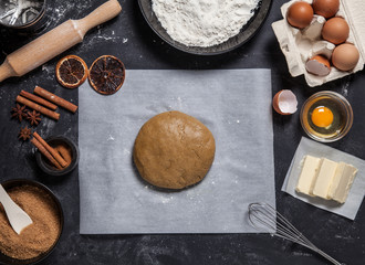 Bakery ingredients, eggs, flour, butter and other. Raw dough with oil on kitchen table flat lay. Bakery, recipe, home cooking concept. Raw dough on parchment paper.