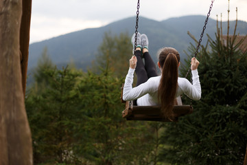Girl riding on a swing with Carpathians mountain on the background. Happy woman enjoys and relaxes on her vacation.