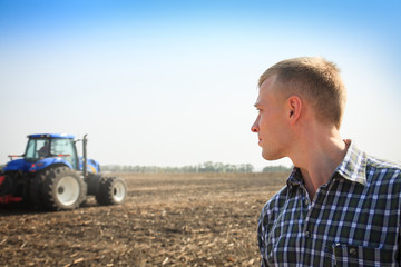 Wall Mural - Young man in a field and a tractor on a background.